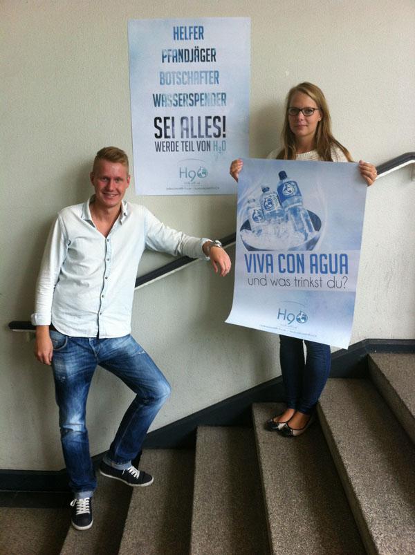 Schüler und Schülerin mit Plakaten